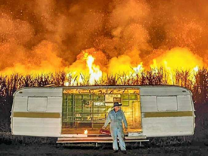 FIELD OF FIRE: Adam Hourigan's photograph of Eric Lyons and the iconic caravan on the Yamba Rd at Palmers Island was part of his portfolio that won the Nikon-Walkley Award.