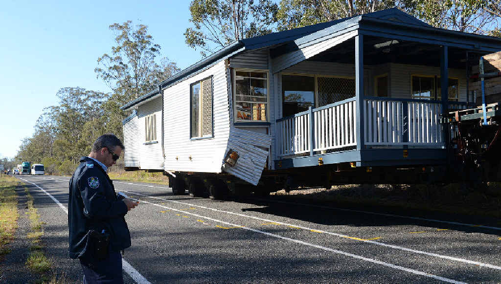 HOUSE CRASH: A police officer checks the scene of a crash on the Bruce Hwy where a car hit a truck.