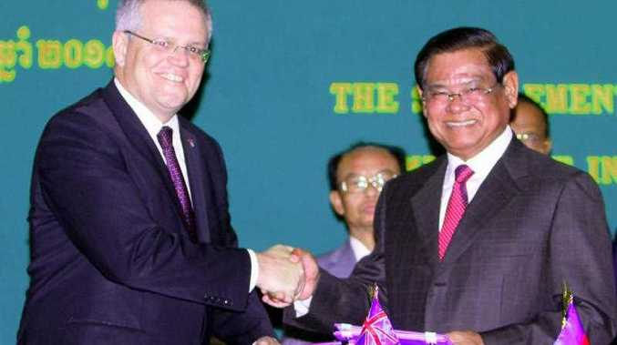 Cambodia's Deputy Prime Minister and Minister of Interior Sar Kheng (R) and Australia's then Immigration Minister Scott Morrison shake hands after signing a memorandum of understanding in Phnom Penh on Sept. 26, 2014, concerning resettlement in Cambodia of refugees rejected by Australia.
