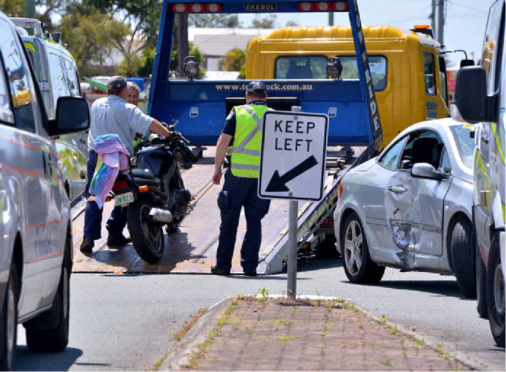 CLEAN UP: Police were busy yesterday at a bike crash in Caloundra, a caravan accident (top right) and a creatively parked car (bottom right).