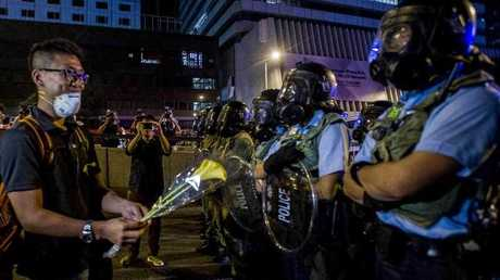 A demonstrator offers a flower to riot policemen during a pro-democracy protest in Hong Kong on September 28, 2014.