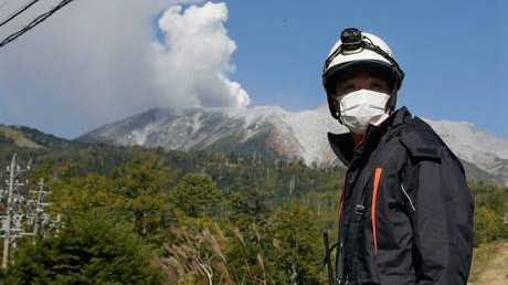 A local fire brigade worker blocks the road to Mt. Ontake (rear), the 3,067-meter volcano