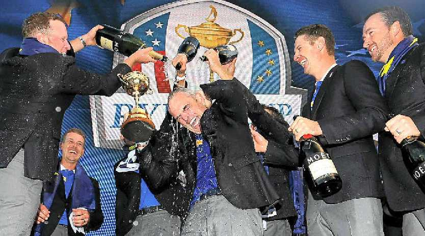 CHAMPAGNE MOMENT: Europe team captain Paul McGinley lifts the Ryder Cup trophy as he is sprayed with champagne by Jamie Donaldson (left).