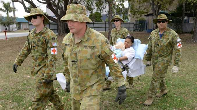 QUICK RESPONSE: RAAF health personnel carry a foreign national whose daughter has a broken leg to an ambulance in the course's scenario.