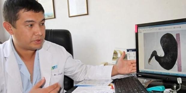 Bishkek Hospital's senior professor of surgery, Bahadir Bebezov examines the hair ball. Photo / YouTube
