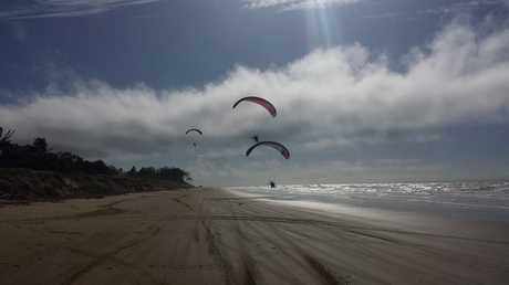 Paragliders soar over a beach in Yeppoon.