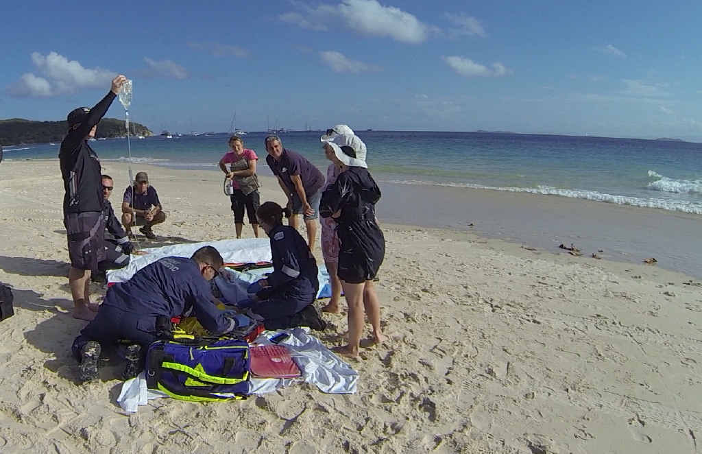ON SCENE: Paramedics treat a woman on Great Keppel Island after a boating accident on Saturday.