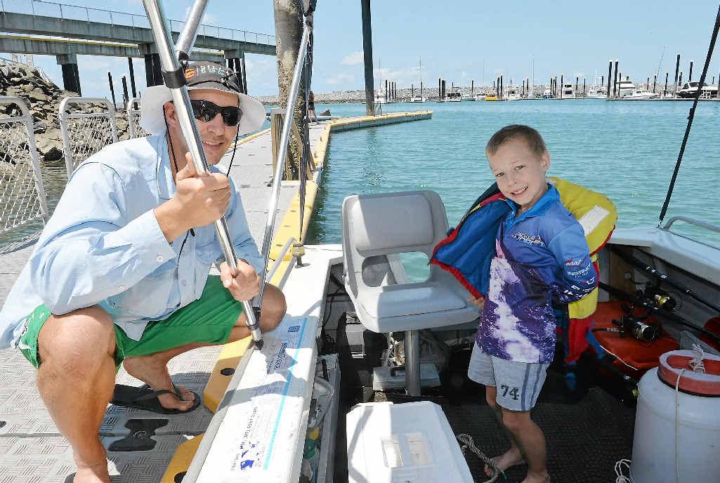 Lee Hokins and his son Marchall, at the boat ramp at the Mackay Marina, can see both sides.