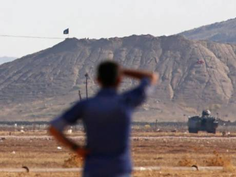An Islamic State of Iraq and the Levant (ISIL) flag flies on the hill above the town of Kobani