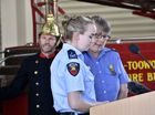 QFES, Remembrance day at Kitchener Street fire station for fire fighters who have lost their lives. Reading the Honour Roll: Katie Connolly (left) and Vicki Searle, with firefighter Lester Naumann . Photo: Bev Lacey / The Chronicle