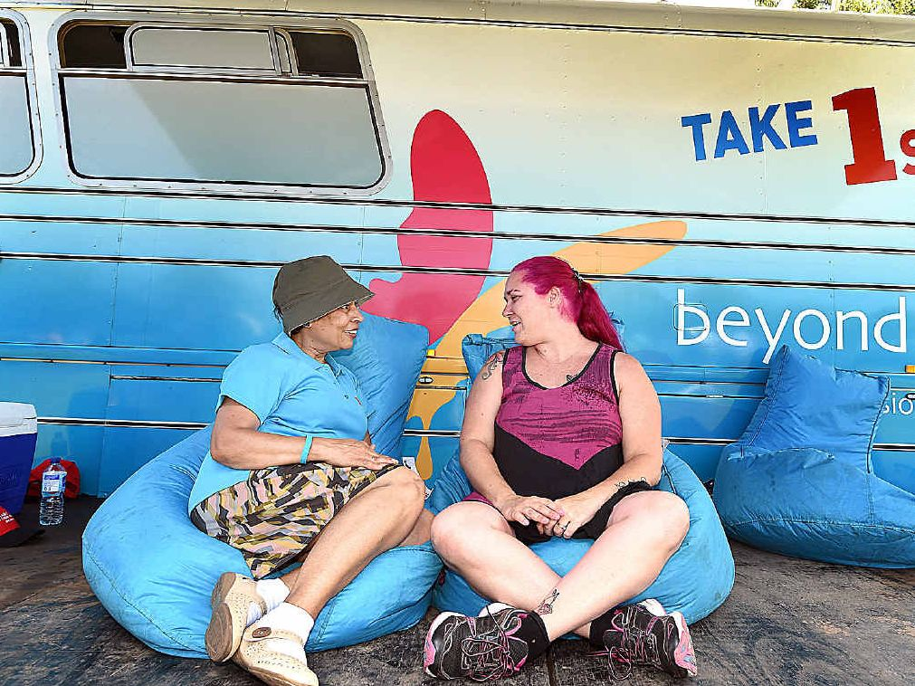 Beyondblue's Linda Shepherd and stallholder Carmel North relax in front of the beyondblue national roadshow's Big Blue Bus.