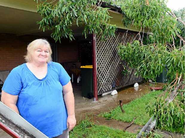 OUT ON A LIMB: Stephanie Barford inspects the damage after a tree fell on her flat during Rockhampton's big wet before the Australia Day weekend in 2013.