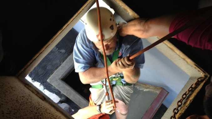 Neil Allport being lowered through the access ports at the top of the Gladstone Metro Hotel.
