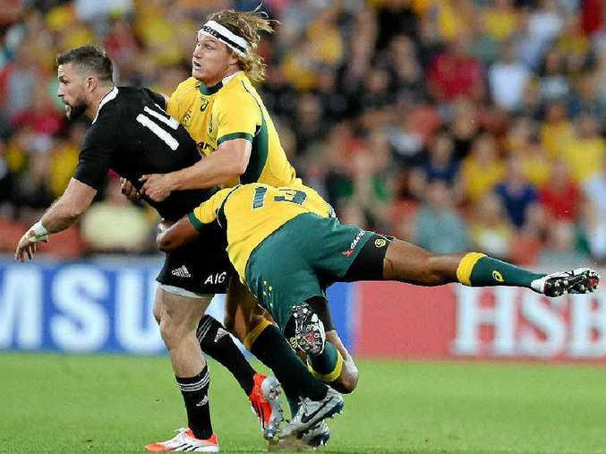 GOTCHA: Wallabies captain Michael Hooper, centre, and teammate Tevita Kuridasni tackle the All Blacks' Cory Jane in Brisbane last night.