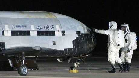 Technicians examining the X-37B unmanned spaceplane shortly after landing at Vandenberg Air Force Base, Calif
