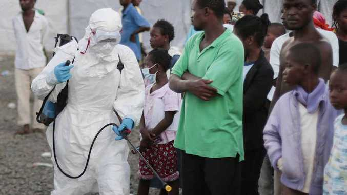 A medical worker sprays people being discharged from the Island Clinic Ebola treatment centre in Monrovia, Liberia.