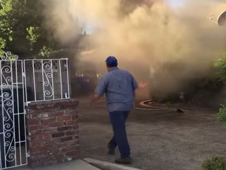 The dramatic rescue of a man from a burning home was captured on video