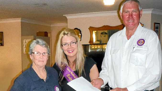VIVACIOUS HAIRDRESSER: Lions Quest committee members Margaret Roberts and Athol McQueen present a sash to Personality Quest entrant Amanda O'Reilly.