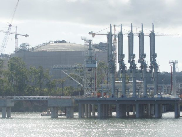 The APLNG site, including loading arms on the dock and an LNG tank, as seen from the quarterly construction cruise on Gladstone harbour, in May 2014.