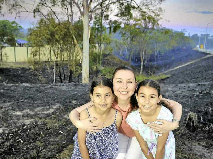 WHAT A DAY: Terri Samuel was relieved to hug her two daughters, Jayde, 9, and Maddison, 12, on Tuesday after their school was evacuated during a wild fire. Fire crews responded quickly to the blaze and kept several properties safe.
