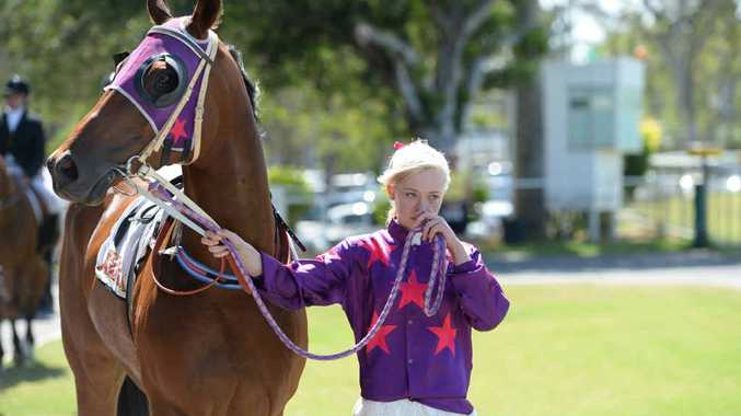 SOLEMN GOODBYE: Rockhampton's Zoe White leads a horse in the entourage at renowned jockey Carly-Mae Pye's funeral service at Callaghan Park.