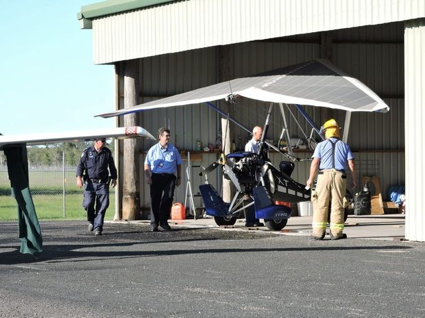 Maryborough Police and Fire officers inspecting a Microlight Airborne XT-912 at the Maryborough Aero Club, following a man catching on fire while refuelling it.