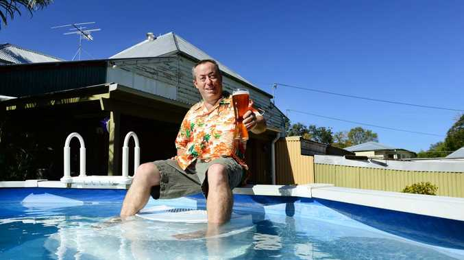 COLD ONE: Tony Brown of Sadliers Crossing cools off with a cold beer and a dip in the pool to escape the hot weather. David Nielsen