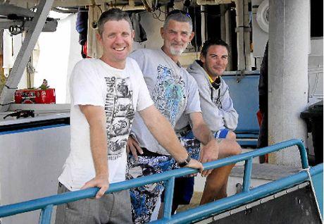 IN DEEP: Warren Harris and Smiley with fisherman Chris Ellis on board trout boat Karen-Ann.