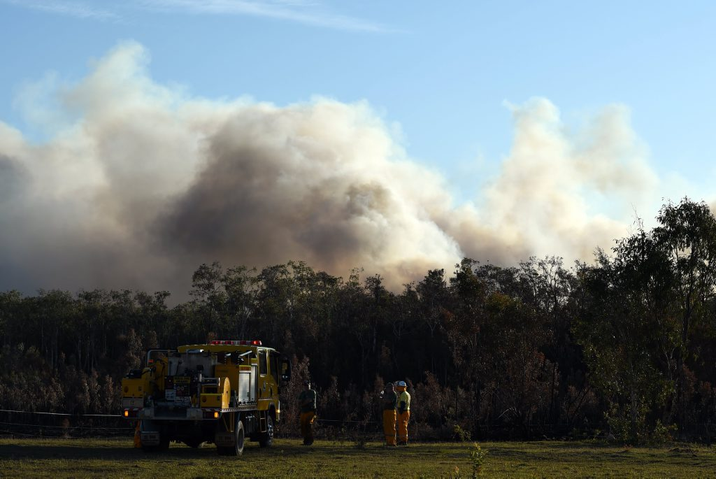 A Toorbul Rural Fire Service crew waits on standby as a bushfire burns near Bestmann Rd, Ningi, on Saturday, October 25, 2014. Photo Jorge Branco / Caboolture News