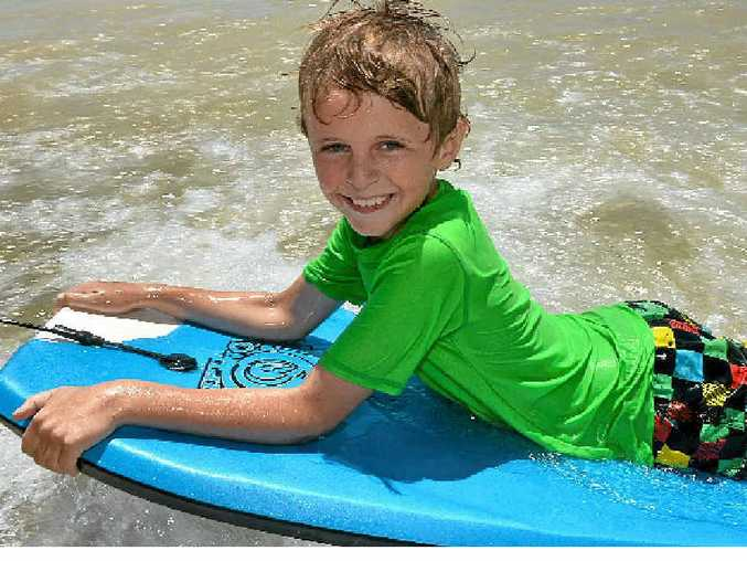 COOLING OFF: Eight-year-old Ned Crowley cools downs with a board ride at Mooloolaba Beach.
