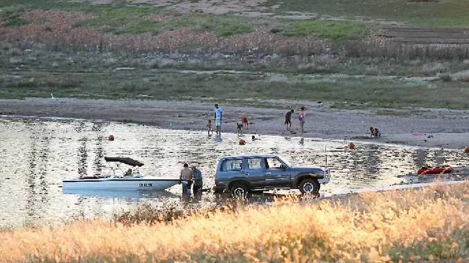 COOLING OFF: Residents dip their toes in the cool waters of the Fairbairn Dam as a reprieve from the sweltering sun.