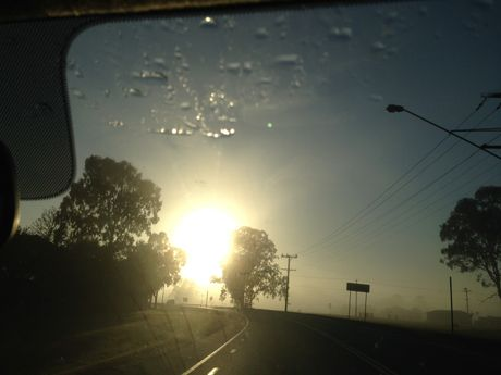 The sun rises through the fog at Caboolture.
