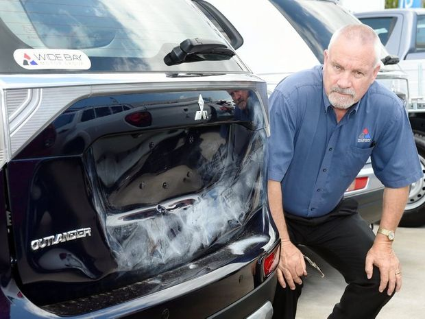 General sales manager Adrian Eustice looks over the damage to a Mitsubishi Outlander following an attack by vandals.