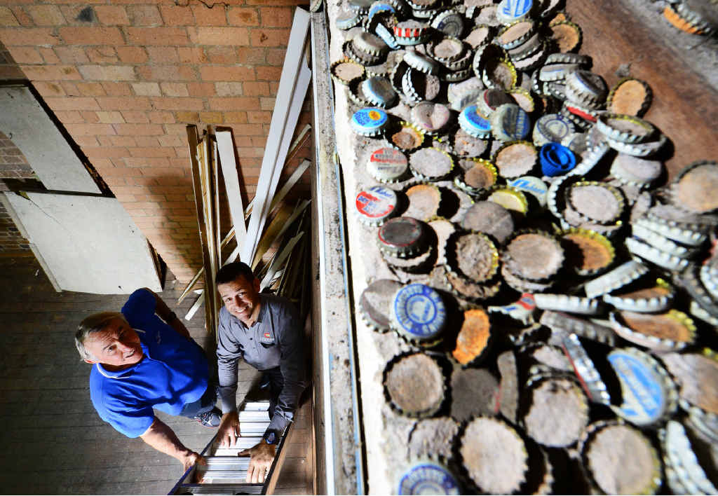 RARE FIND: Choices Flooring owner Steve Mallet and Peter McMahon, whose family owned McMahon's Soft Drinks, marvel at the unusual discovery of McMahon's bottle caps found in the store's ceiling.