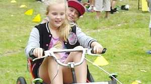 Teven-Tintenbar Public School s 20th Annual Country Fair on Saturday. Anika Shoesmith (seated in billy cart) is pushed by Kya Gaiter.