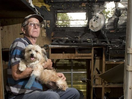 DOWN ON HIS LUCK: Murphys Creek resident Les Collins with his injured dog Pepper in his burnt out caravan. Monday, Nov 3, 2014 . Photo Nev Madsen / The Chronicle