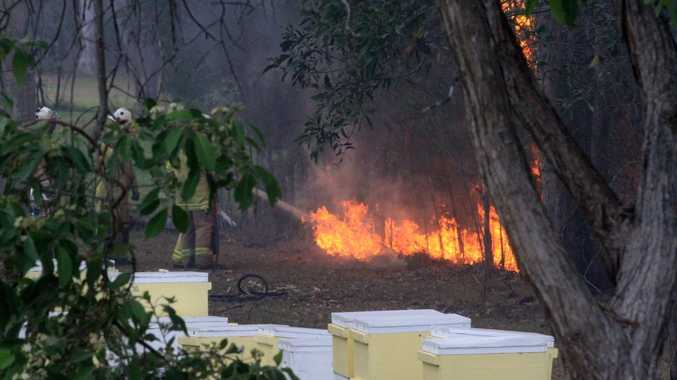 Fire crews battle a grass fire threatening homes at Tiffany Crt in Caboolture on November 3, 2014. Photo Jorge Branco / Caboolture News