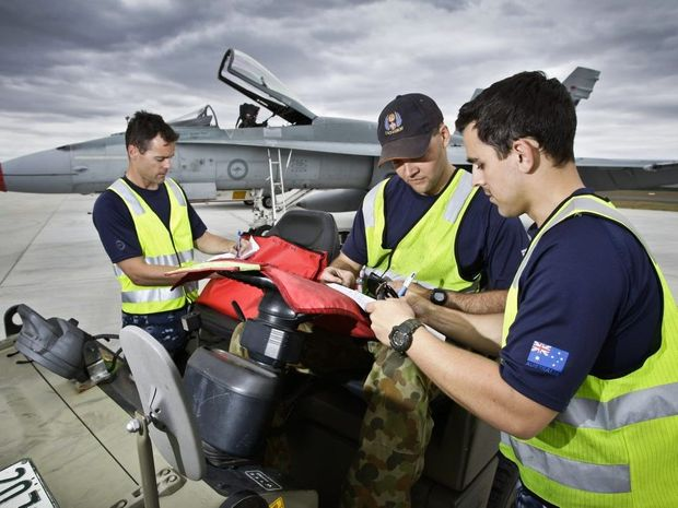 RAAF Aircraft Technicians, (L-R) Leading Aircraftman (LAC) Josh Walsh, LAC Graeme Szynal and LAC Ben Nolte clear maintenance paperwork after the arrival of F/A-18 Hornets at RAAF Base Amberley. The aircraft are on standby to support the G20 Leaders Summit.