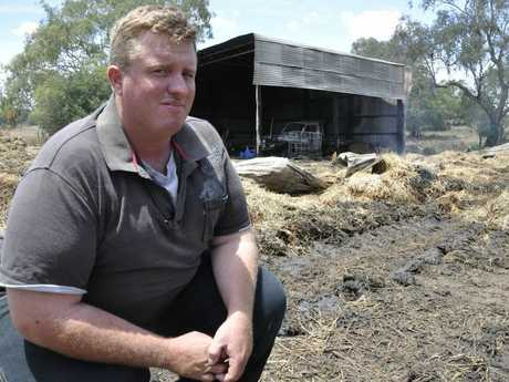 Farmhand Chris Riordan inspects the remnants of a hay shed fire on a property near Pittsworth.