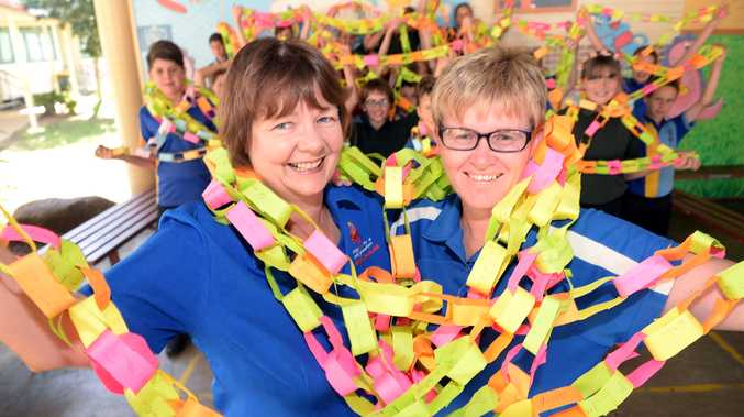 PAPER CHAIN: Kalkie State School staff Marion Crane and Carolyn Caldwell and students helped make a Random Acts of Kindness Chain. Photo: Max Fleet / NewsMail