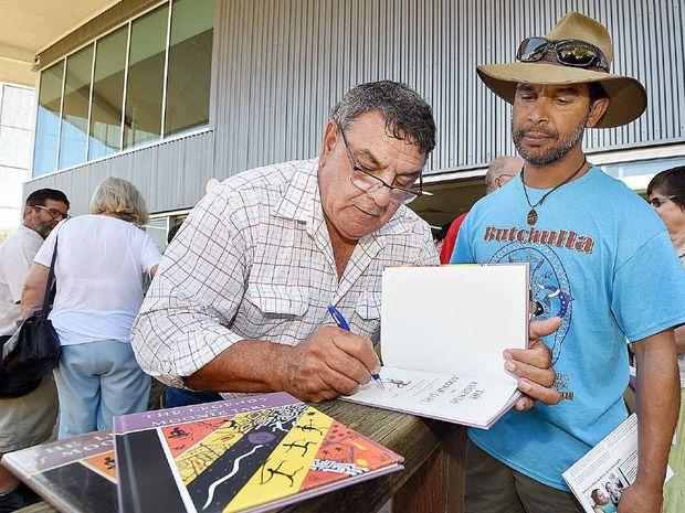 SPECIAL DAY: Glen Miller signs a copy of the book 'The Legends of Moonie Jarl' for Fraser Island ranger Darren Blake.
