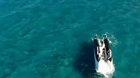 Men wait onboard an upturned catamaran for the RACQ Careflight Helicopter Rescue crew.