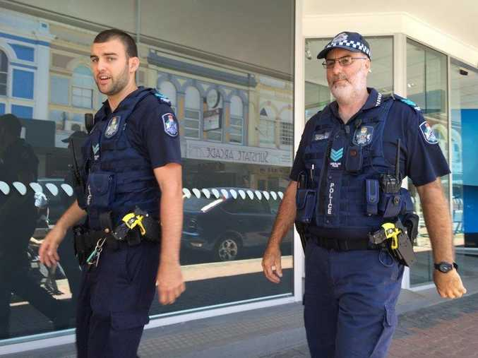 Police officers leaving the scene of a disturbance at Maryborough's ANZ Bank.