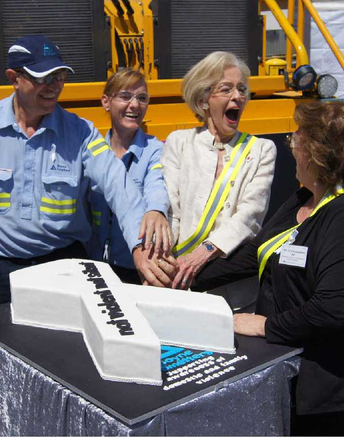 CAMPAIGN SUPPORT: Boyne Smelter Ltd general manager Joe Rea, BSL occupational hygienist Sandra Gooderham, Quentin Bryce and Gladstone MP Liz Cunningham shared a laugh over the incredible white ribbon cake made by Sandra.