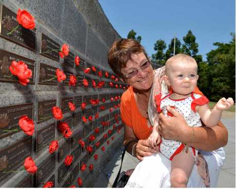 RED WALL: Jennifer Blanch and six-month-old Emma Smith place a poppy for their family members at the Remembrance Day service at Nambour, and at Maroochydore (below) Finn Reeman, 2, and his brother Henry, 4, watched proceedings.