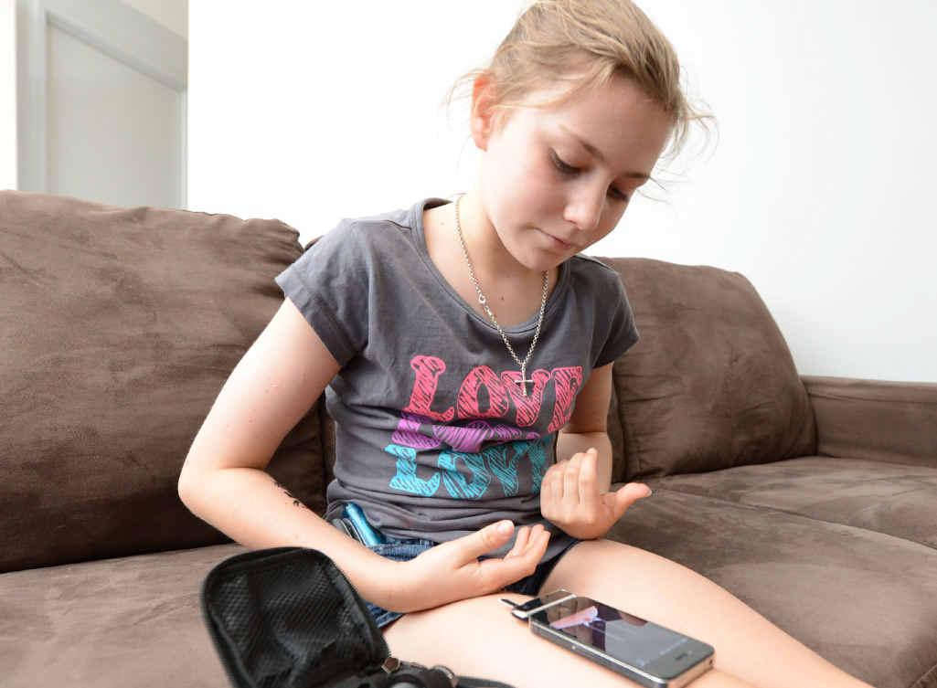 Brianna Norris uses an iPhone attachment and application to monitor her insulin levels.