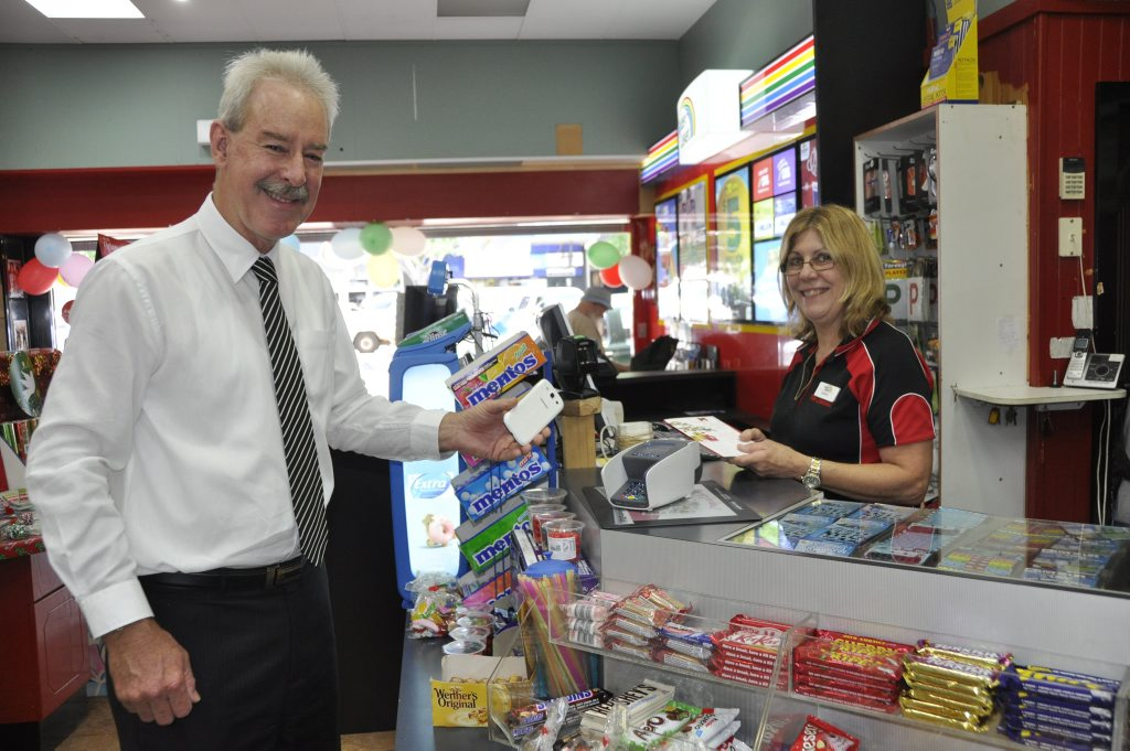Heritage Bank CEO John Minz makes a purchase with the phone app Cash by Optus. He is served by Cheryl Sexton at Ruthven St News. Photo Rachael Murray / The Chronicle