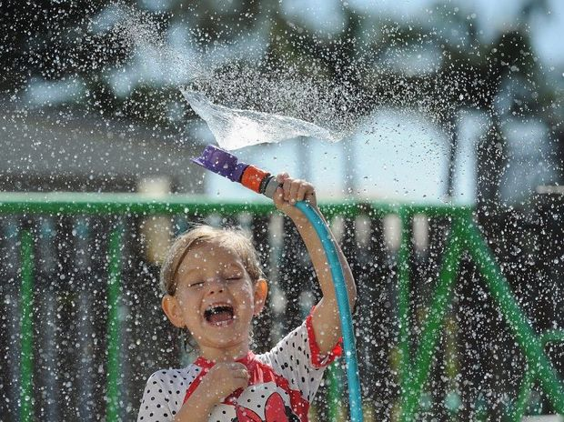 Isabel Corke, 4, cools off in the timeless way under the sprinkler at her home in Granville.