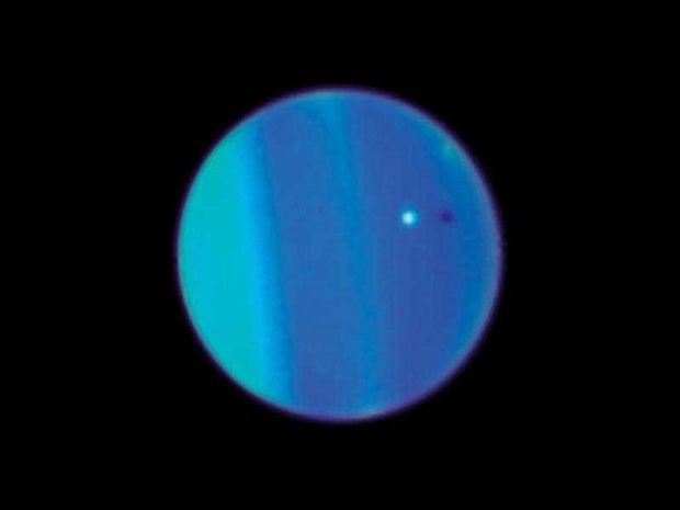 This 2006 image provided by NASA shows an image of Uranus with its moon Ariel, small white sphere, made by the Hubble Space Telescope. A team of Canadian and French scientists discovered a space rock that closely follows the planet's orbit.