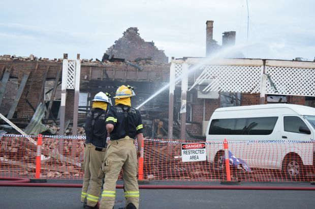 NEW FIRE: Firefighters try to put out a small blaze that has emerged from the wreckage of the Royal Hotel today.
